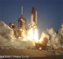 Space shuttle lifting off launch pad